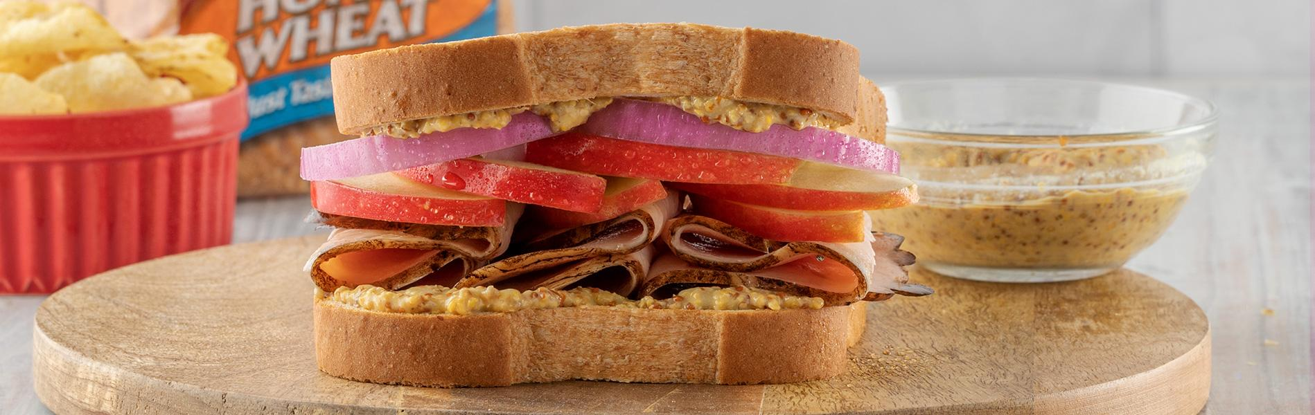 Sandwich with ground mustard, red onion, apples and turkey
