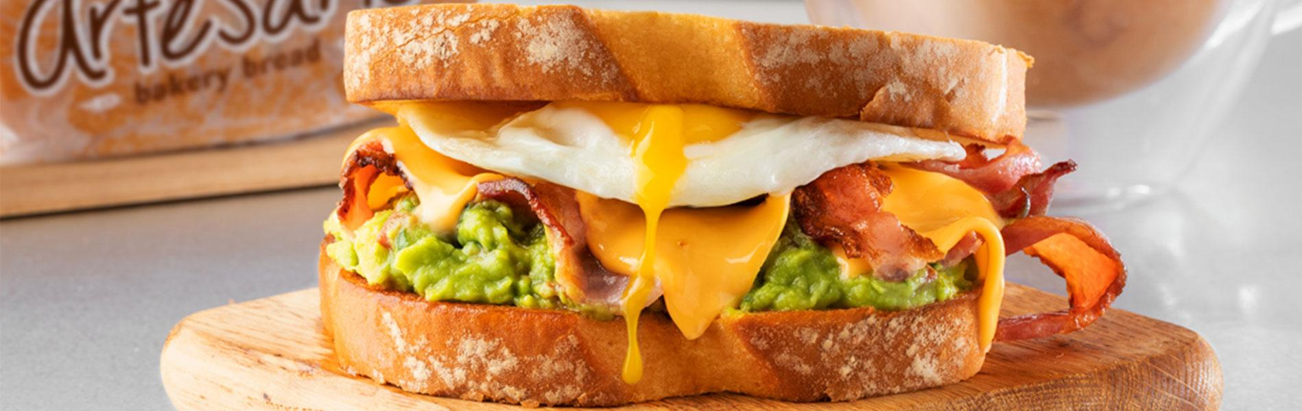 Breakfast sandwich with spicy guacamole, bacon, egg and Cheddar cheese