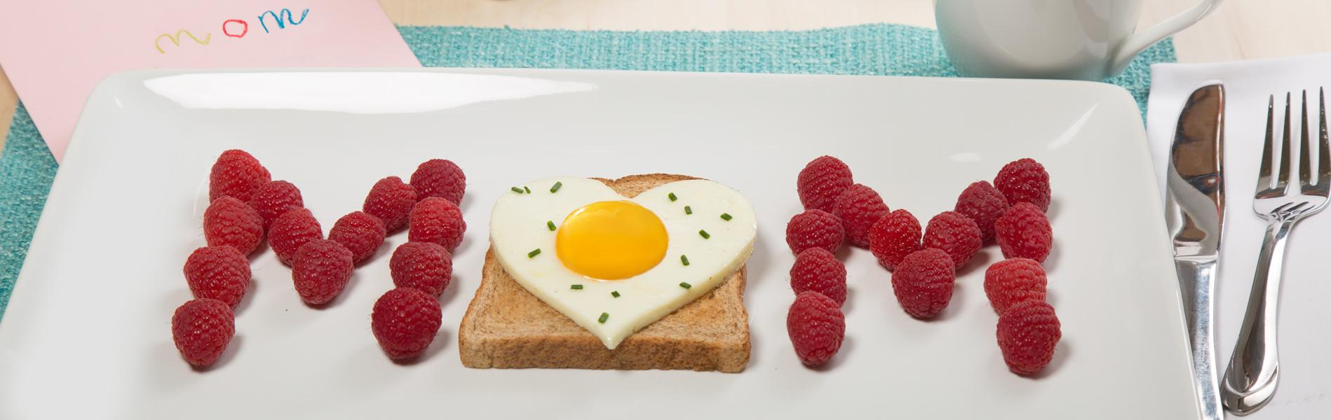 Heart shaped egg on toast with raspberries on the side