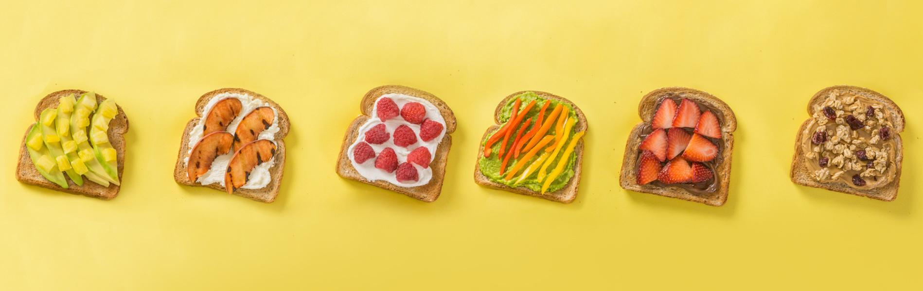 Variety of fruits, avocado and spreads on toast