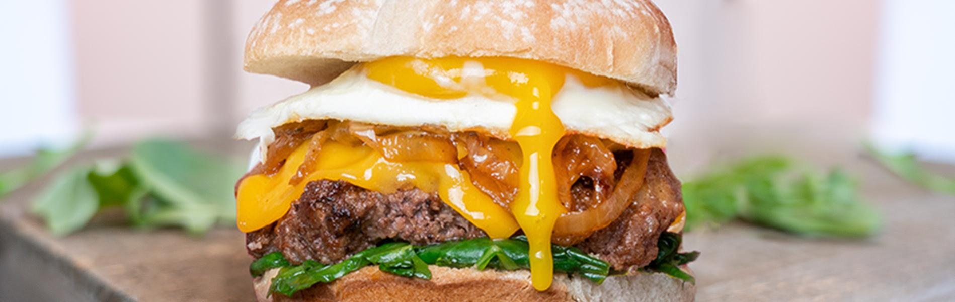 A burger with eggs, onions, cheese and spices