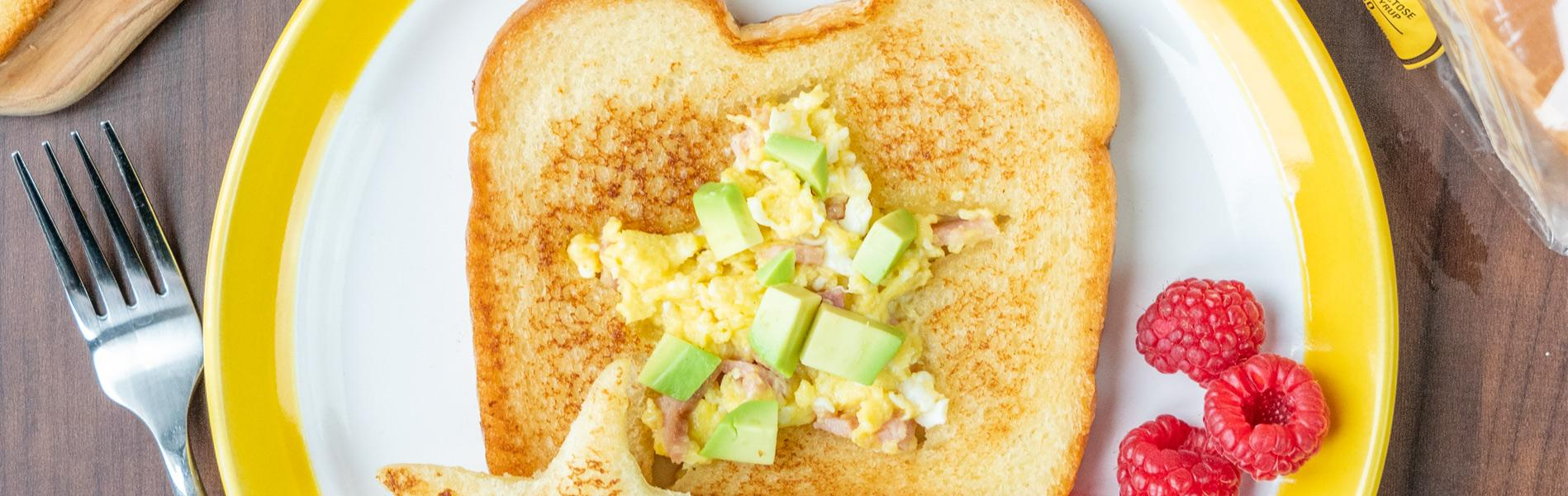 Bread with a star-shaped hole in the center, filled with scrambled eggs, ham, avocado and cheese