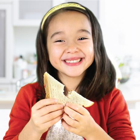 A child smiling while eating a sandwich