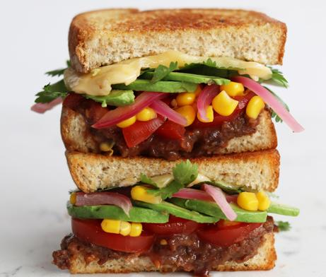 Grilled sandwich layered with veggies, bean, cheese, butter and avocado