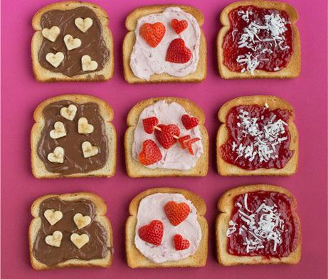 Variety of spread and heart-shaped fruit on toasts