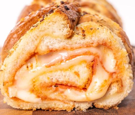 Bread rolled up with cheese, pepperoni, pizza sauce and spices